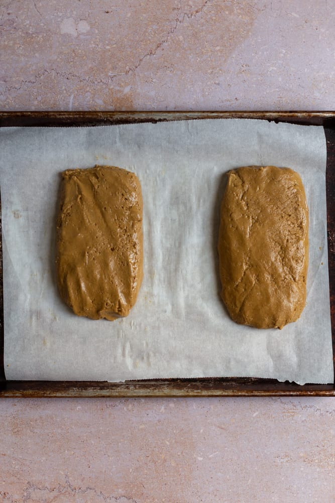 2 unbaked loaves of biscotti cookies on a sheet tray.