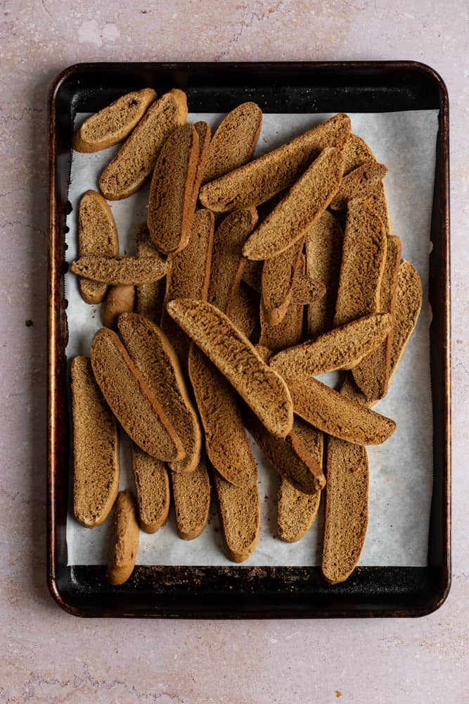 Biscotti cookies piled onto a baking tray lined with parchment paper