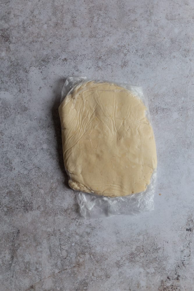 Shortbread dough wrapped in plastic wrap on a gray surface