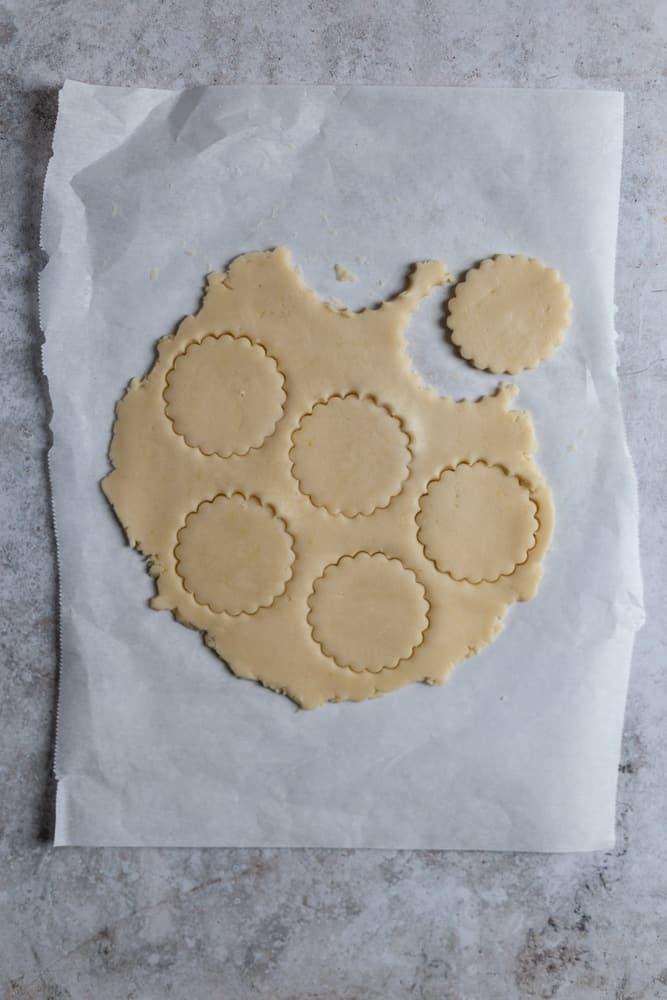 Shortbread dough cut out into cookie shape son a piece of parchment paper