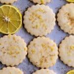 Lemon shortbread cutout cookies on a blue surface