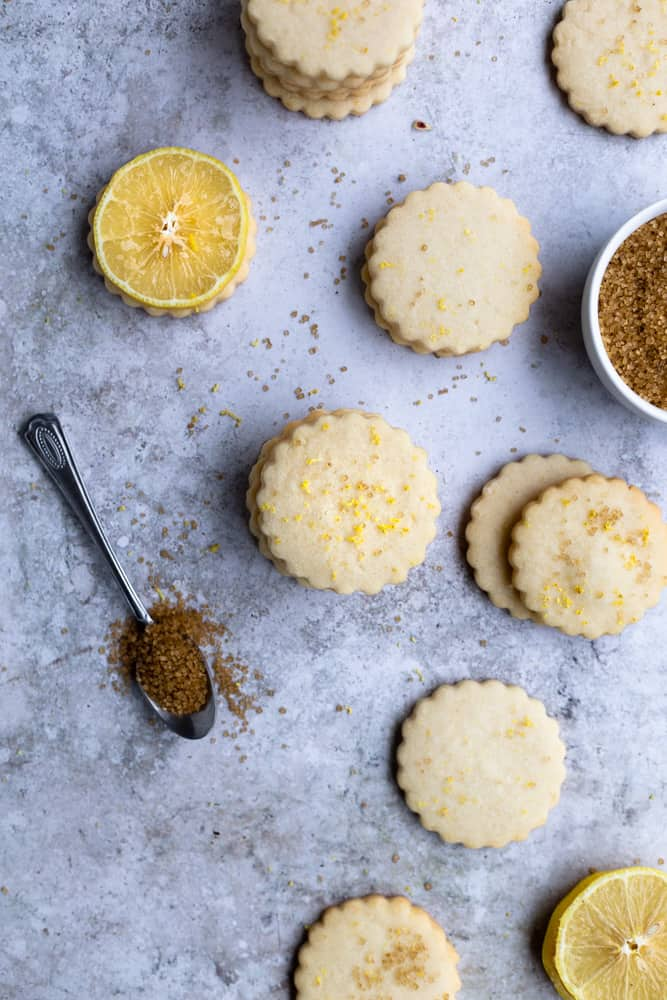 Lemon shortbread cookies stacked in piles on a blue gray surface