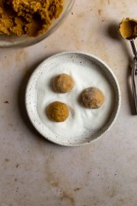 three cookie dough balls rolling in sugar in a bowl