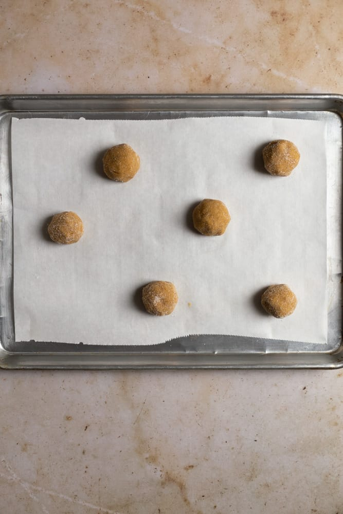 6 cookie dough balls staggerd on a baking tray