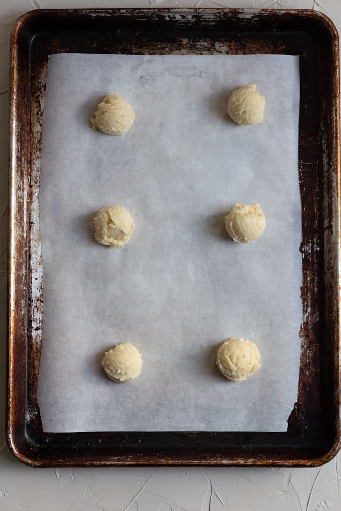 cookie dough balls lined up on a cookie sheet