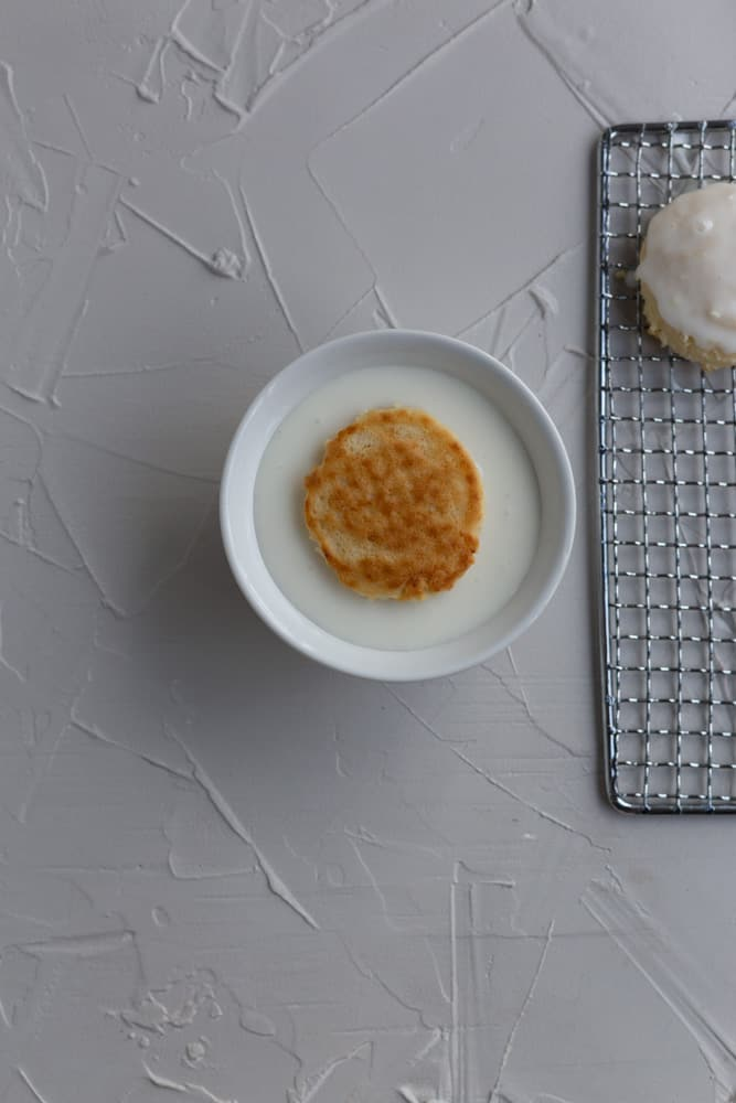 A cookie dunked into a small white bowl of glaze