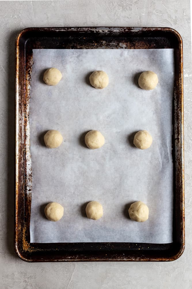 Cookie dough balls lined on a parchment covered cookie sheet