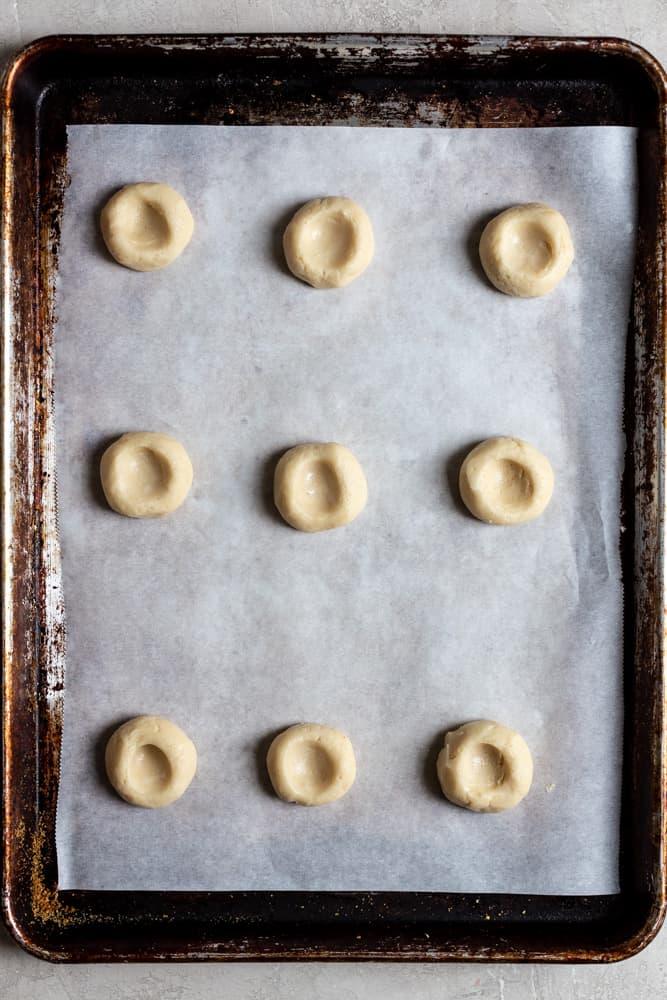 Pressed thumbprint cookie dough on a parchment lined cookie sheet