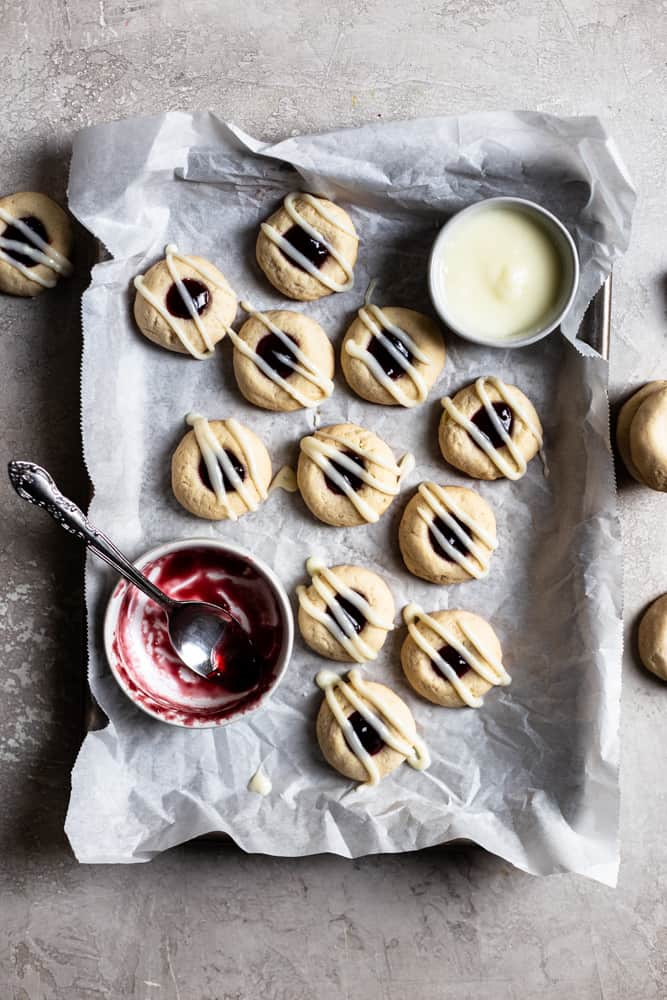 Glazed Raspberry thumbprint cookies on a parchment lined baking tray next to a bowl of jam
