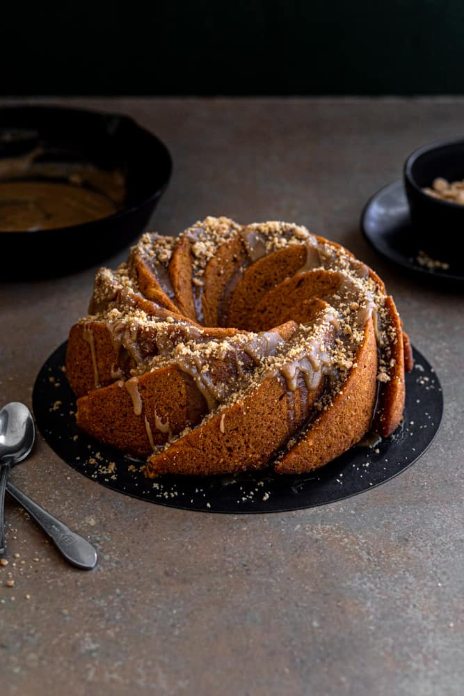 Carrot bundt cake on a black cake plate on a dark beige surface