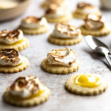 Closeup of a lemon meringue cookie with spoons in the background