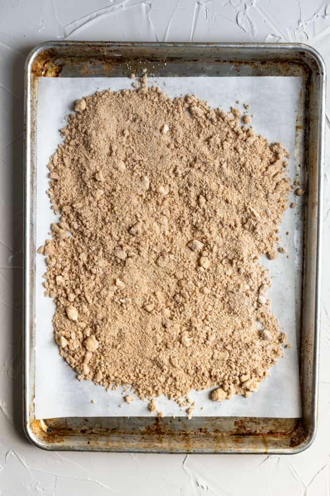 Unbaked streusel laid out on a sheet tray