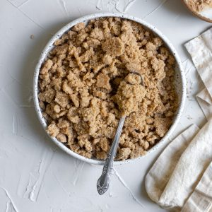 Streusel in a white ceramic bowl with a spoon on a white surface