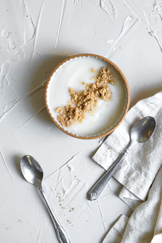 Yogurt topped with streusel in a small bowl on a white surface