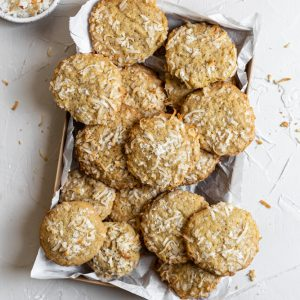 Coconut cookies in a parchment paper lined tray on a white background