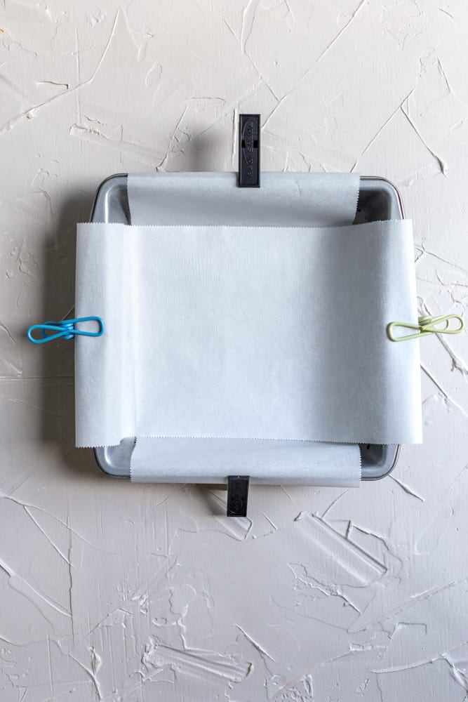 An 8x8 inch pan lined with parchment paper and clips attached to the ends