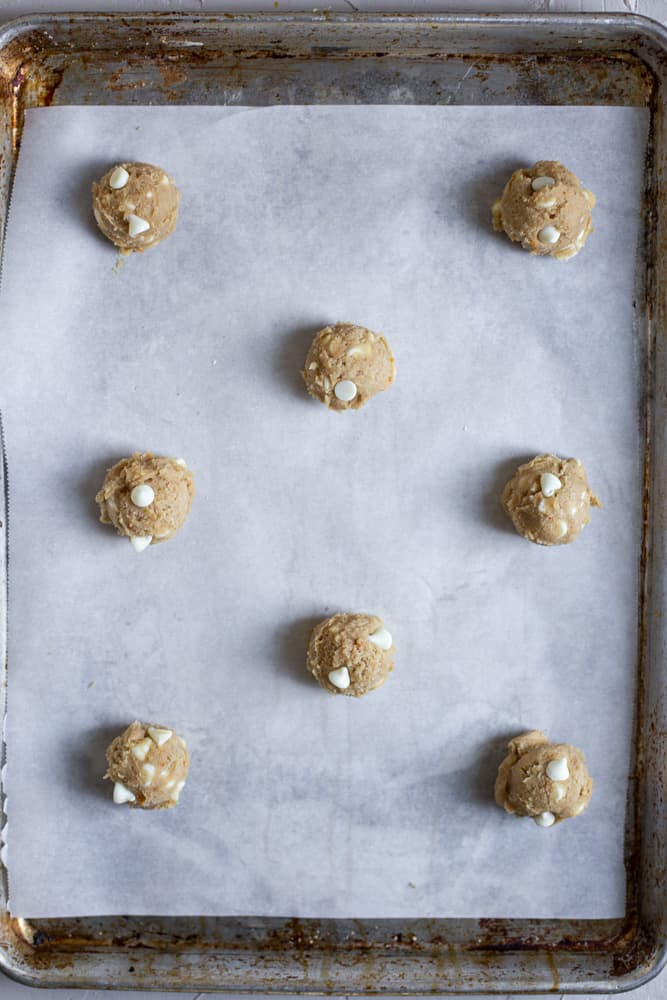 orange cookie dough balls on a parchment lined sheet