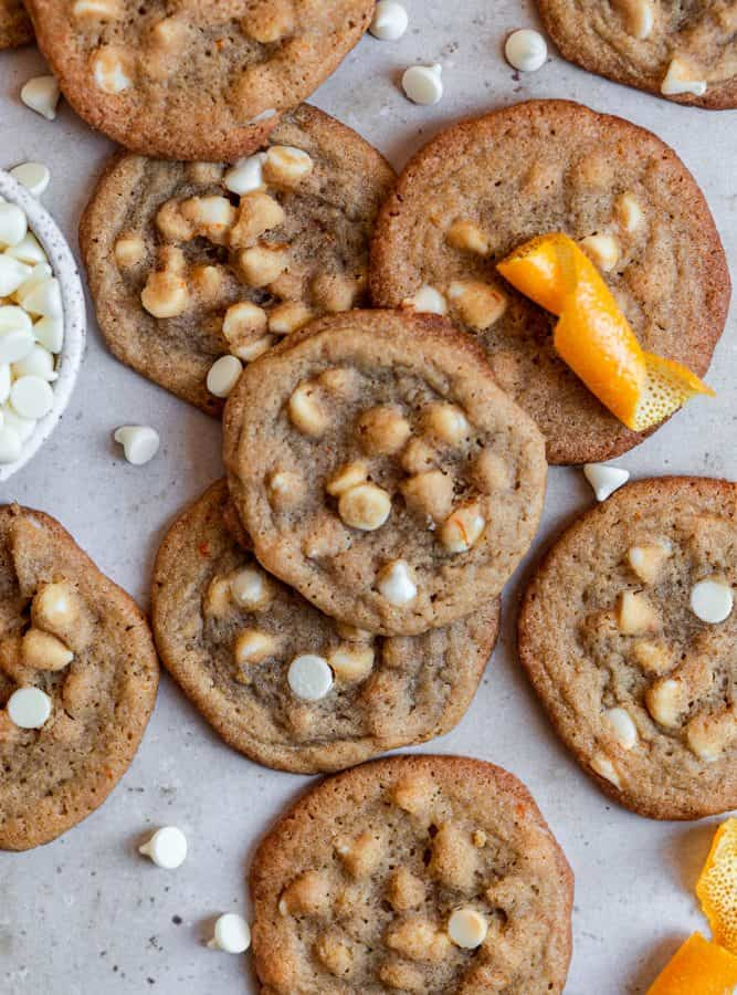 orange cookies with white chocolate chips on a gray surface