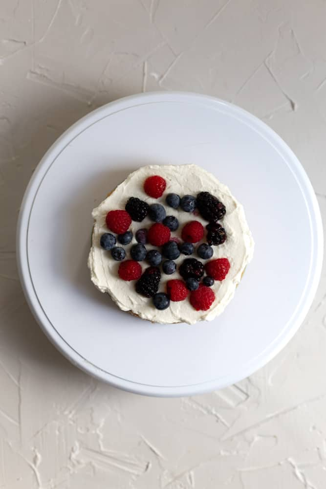 A cake layer topped with mascarpone chantilly cream and fresh berries
