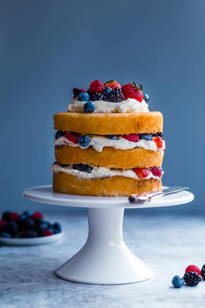 3 layered naked cake with white cream frosted layers and berries sitting on a white cake stand