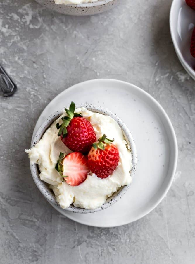 Mascarpone frosting in a bowl on a white plate topped with strawberries