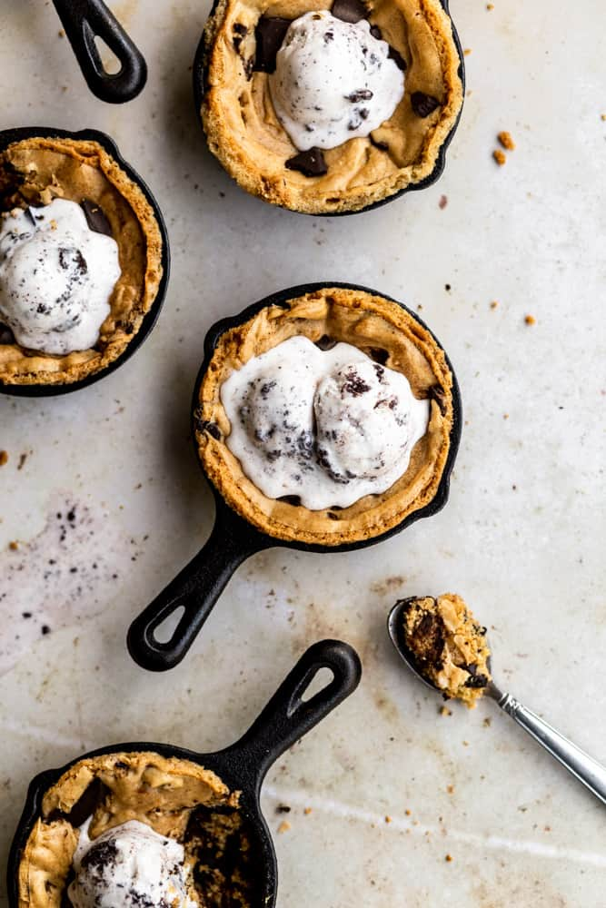 Mini skillet chocolate chip cookies on a beige surface