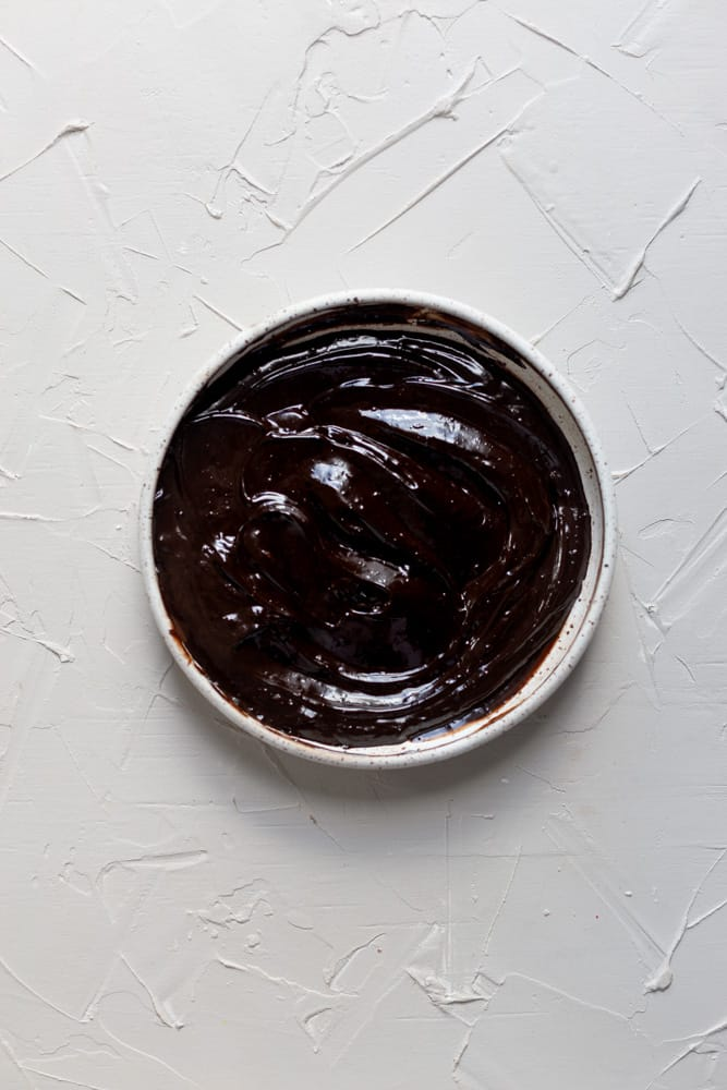 chocolate ganache in a bowl on a white surface