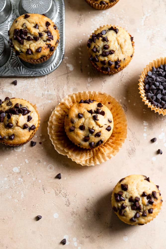 Chocolate chip banana muffins with the liners peeled off on a beige surface