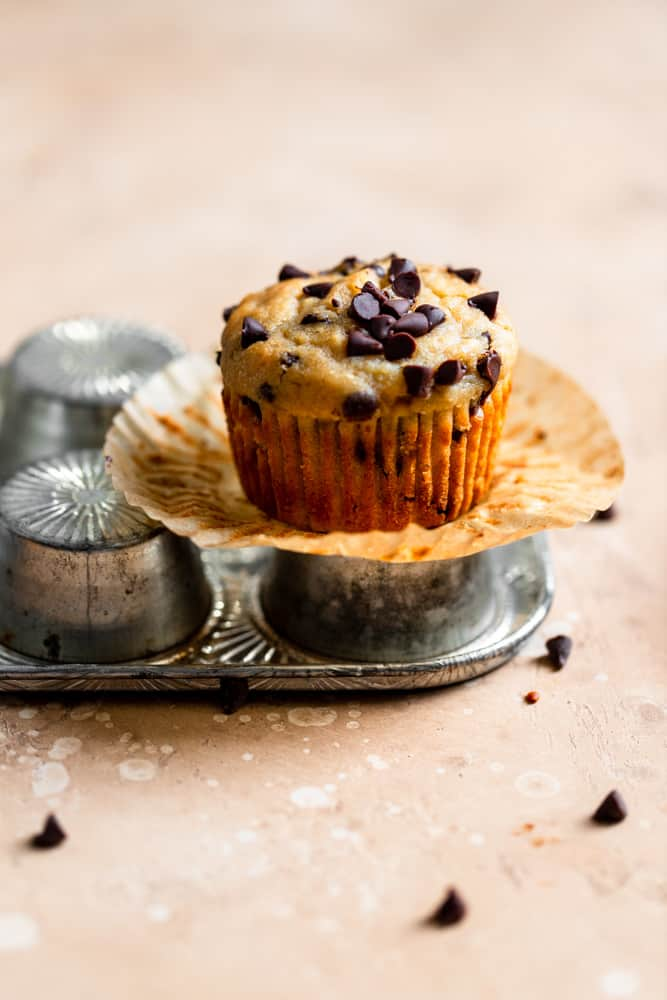 A chocolate chip banana muffin sitting on top of an overturned muffin pan