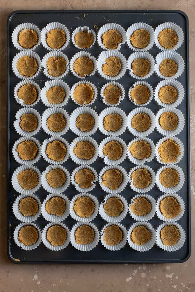 A mini muffin tin lined and filled with graham cracker crust
