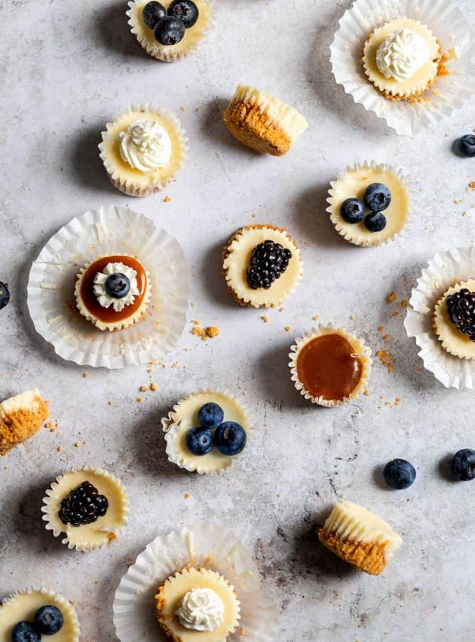 Mini cheesecakes topped with different toppings like caramel and berries on a white surface