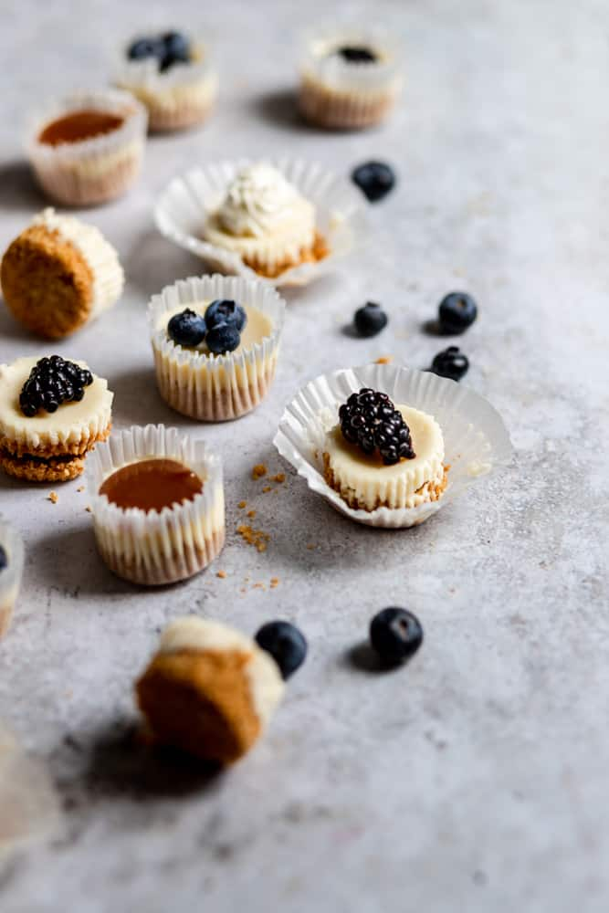 Mini cheesecake bites topped with blueberries, blackberries, and homemade caramel sauce on a gray surface.