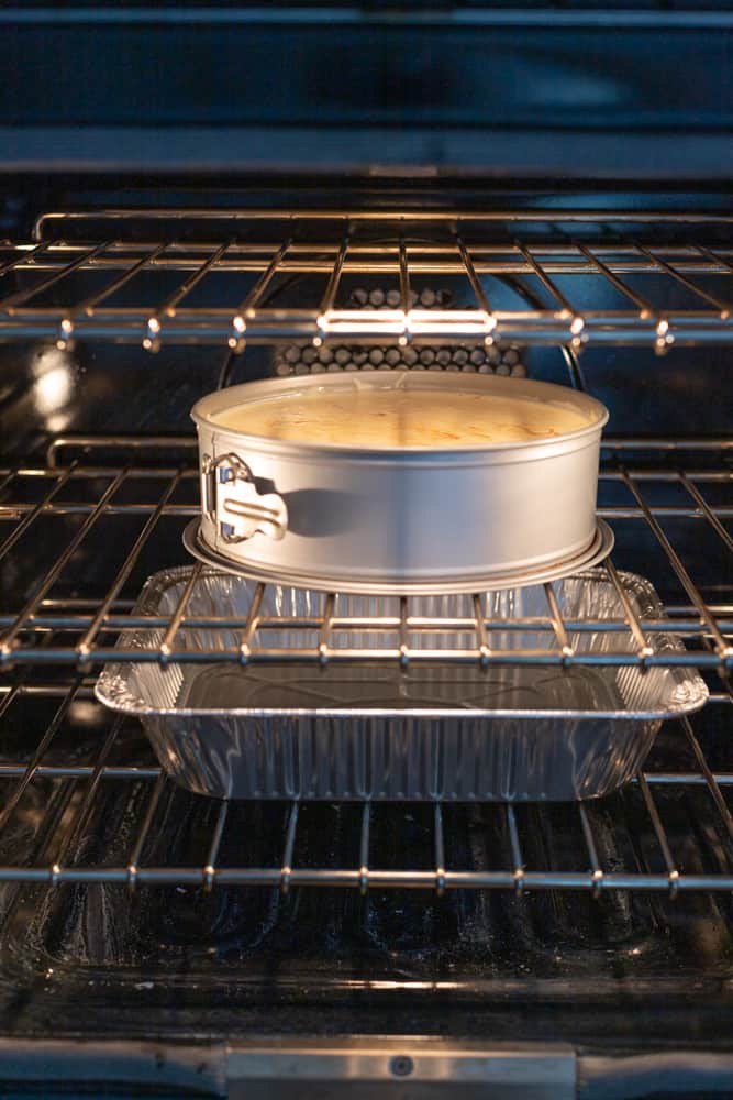 A cheese cake on the top rack of the oven with a pan of water in the bottom