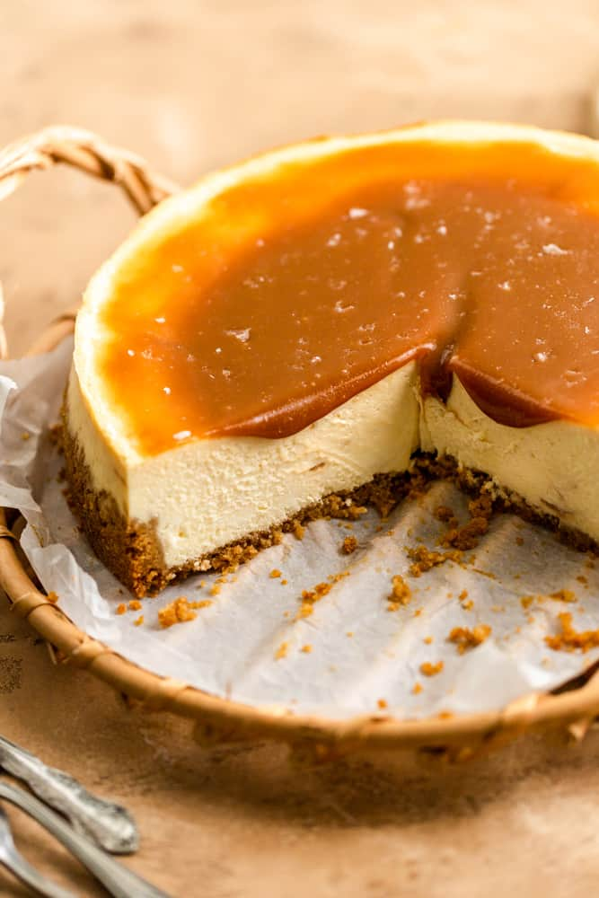 A cheesecake with a slices taken out of it on a wooden tray with caramel sauce on top.