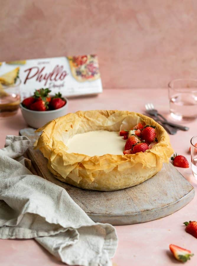 Side view of a strawberry cheesecake made with phyllo dough topped with strawberries on a pink surface