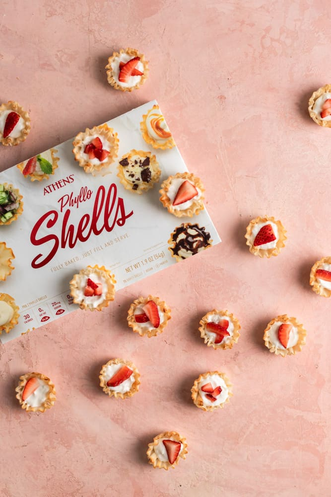 Cheesecake in little phyllo dough shells on a pink surface