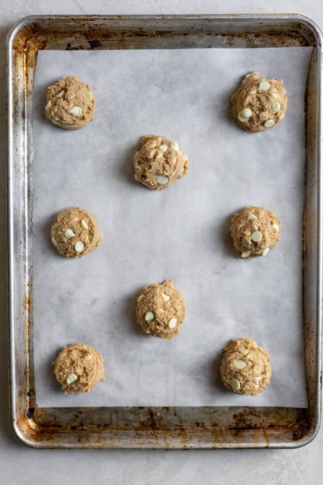 Cookie dough balls staggered on a parchment paper lined cookie sheet