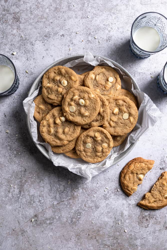 White Chocolate chip cookies in a parchment paper lined bowl next to 3 cups of milk on a textured gray surface.