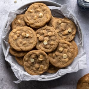 White chocolate chip cookies in a bowl that is layered with parchment paper on a gray textured surface
