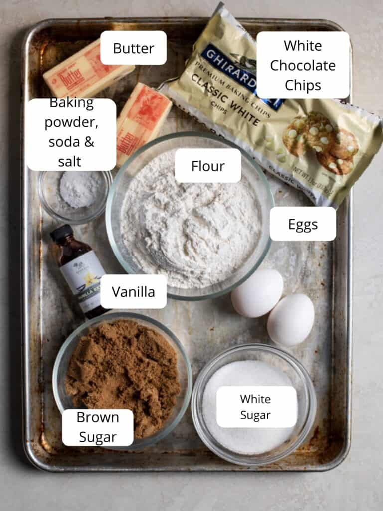 Ingredients for white chocolate chip cookies on a sheet tray