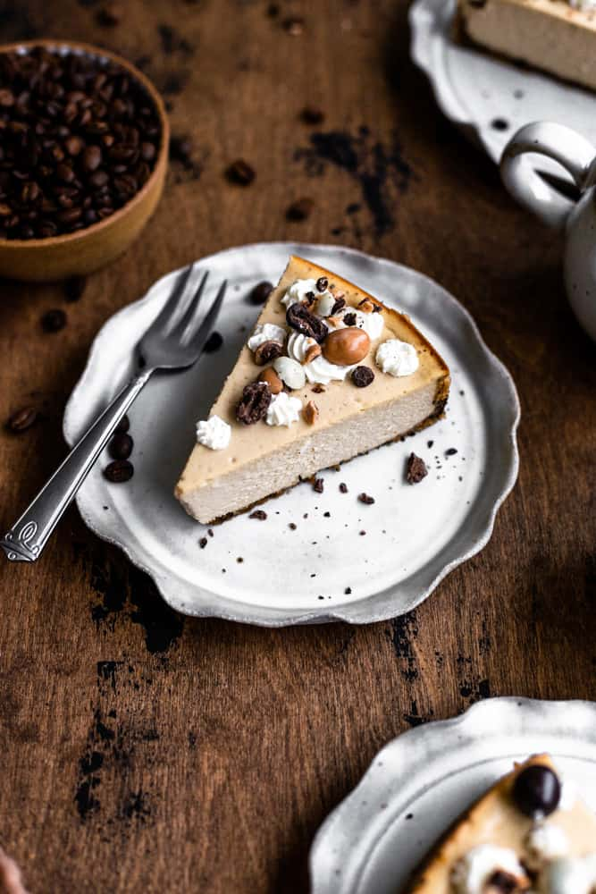 A slice of coffee cheesecake on a gray ruffled plate on a wooden surface