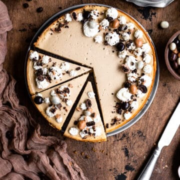 A cheesecake decorated with whipped cream and chocolate covered espresso beans with 3 slices cut on a wooden surface