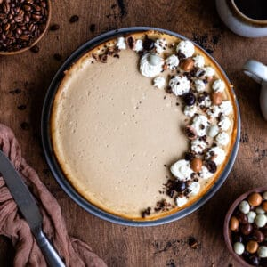 Coffee cheesecake decorated with whipped cream and chocolate on a wooden surface