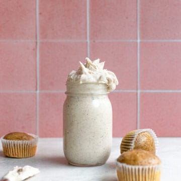 Espresso buttercream in a mason jar next to 3 unfrosted cupcakes